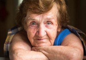30744350 - close-up portrait of old woman sitting at table in his house.